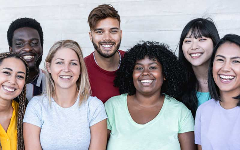 7 people, 3 in back and 4 in front. White, Asian, Latino, African American skin tones. In an article on how far back someone can trace their ancestry.