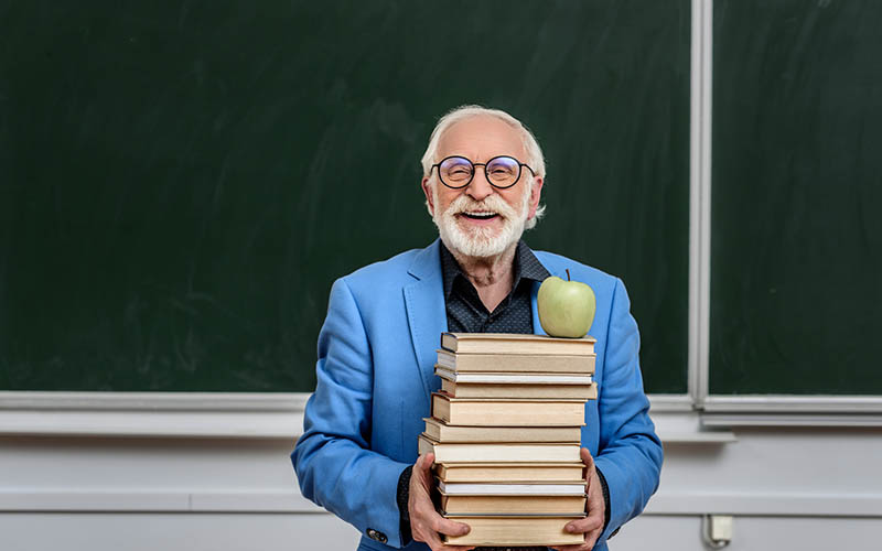 Man holding textbooks with an apple on top. Appears to be an academic, many careers in genealogy are academic.